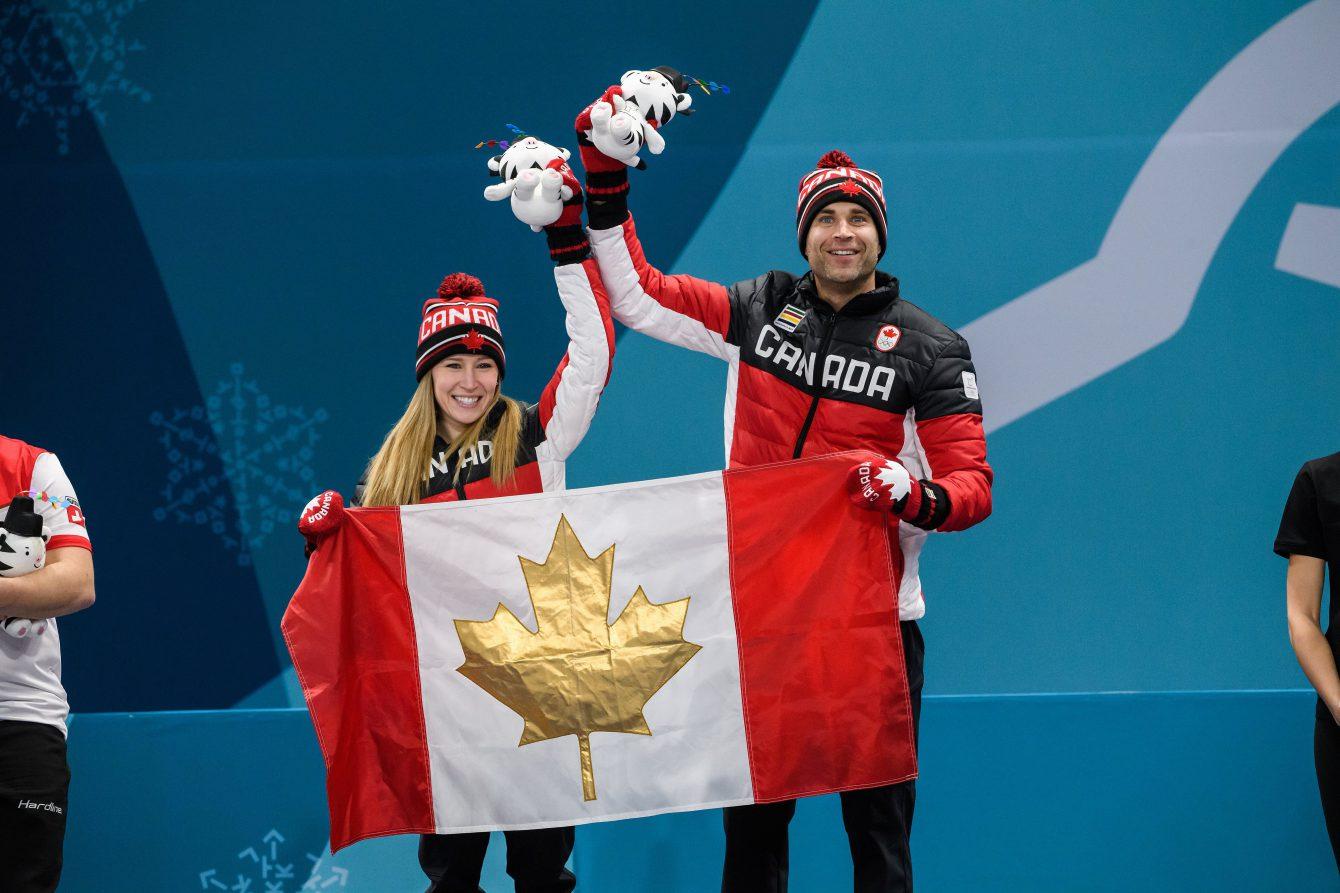Deux athlète sur un podium avec des toutous et un drapreau