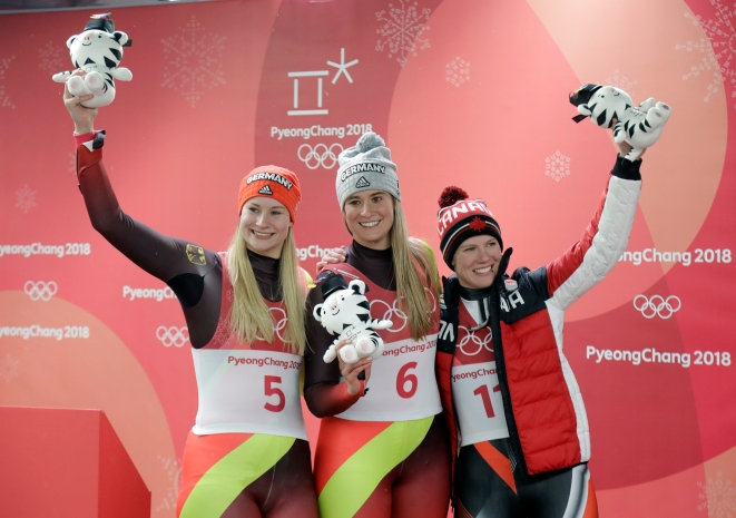 De gauche à droite, la médaillée d'argent Dajana Eitberger de l'Allemagne, la médaillée d'or Natalie Geisenberger de l'Allemagne, et Alex Gough, médaillée de bronze, à l'épreuve simple de luge aux Jeux olympiques de PyeongChang, le 13 février 2018. (AP Photo/Wong Maye-E)