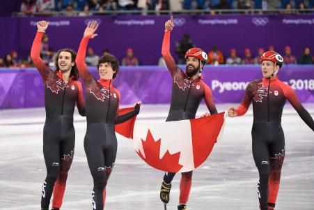 De gauche à droite: Samuel Girard, Charle Cournoyer, Charles Hamelin et Pascal Dion tiennent le drapeau canadien