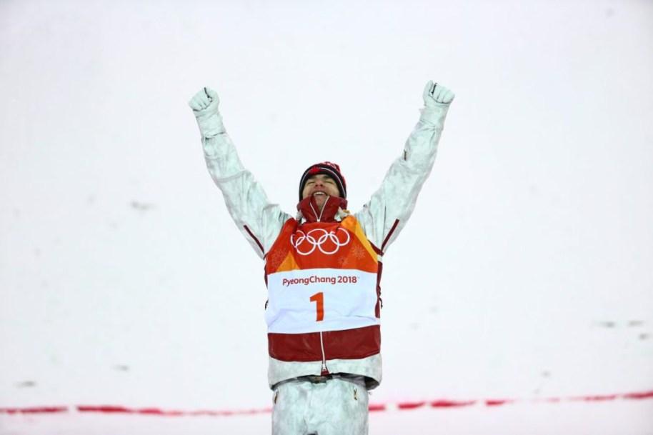 Mikaël Kingsbury, bras en l'air, célèbre sa victoire sur le podium
