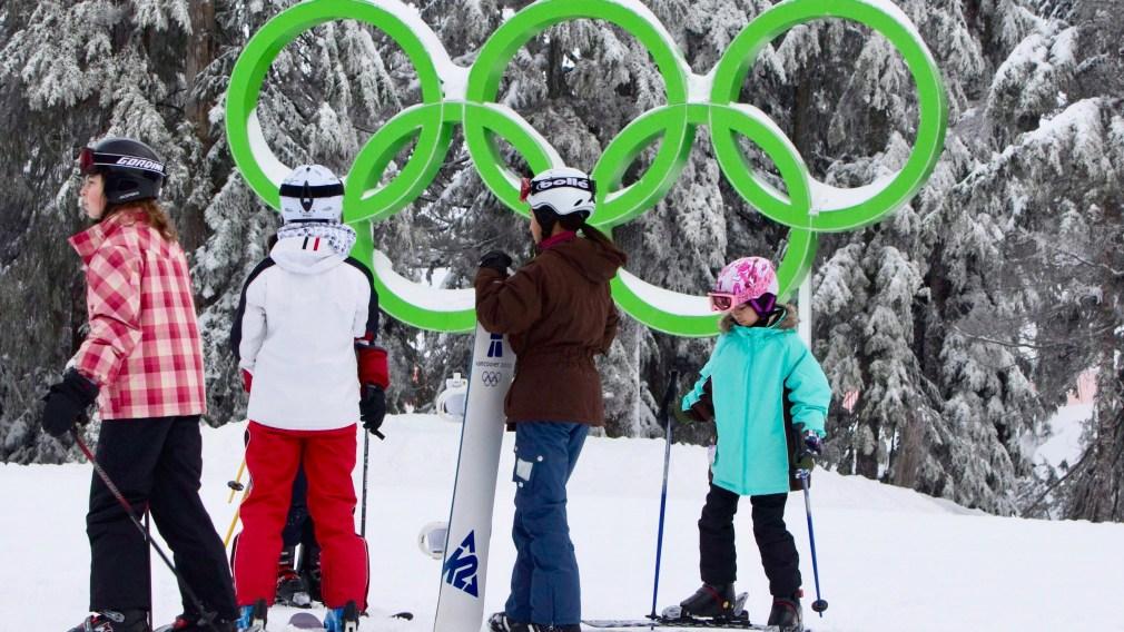 Quatre enfants en ski, les anneaux olympiques en arrière-plan