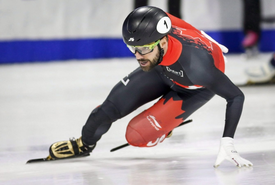 Charles Hamelin négocie une courbe, main sur la glace.