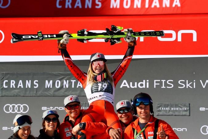 La médaillée d'argent Roni Remme célèbre sur le podium avec ses coéquipiers après l'épreuve de combiné alpin à la Coupe du monde de Crans-Montana, en Suisse, le 23 février 2019. (AP Photo/Alessandro Trovati)