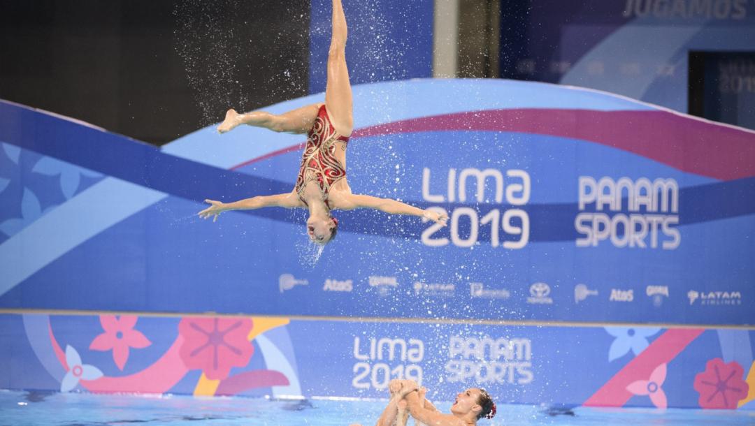Une nageuse artistique en plein saut hors de l'eau