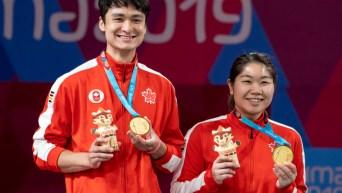 Deux athlètes montrent leur médaille d'or