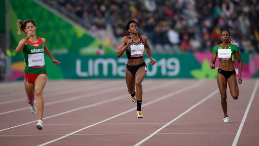 Trois athlètes courent sur le circuit d'athlétisme