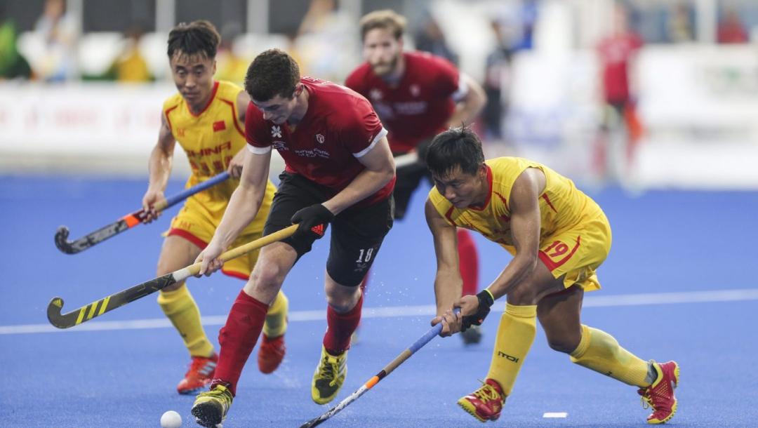 Trois joueurs de hockey sur gazon en action