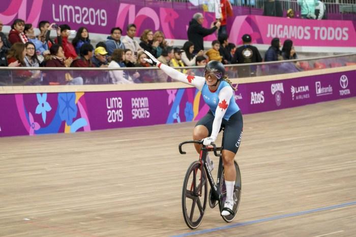 Kelsey Mitchell souriante sur son vélo après avoir remporté une médaille.