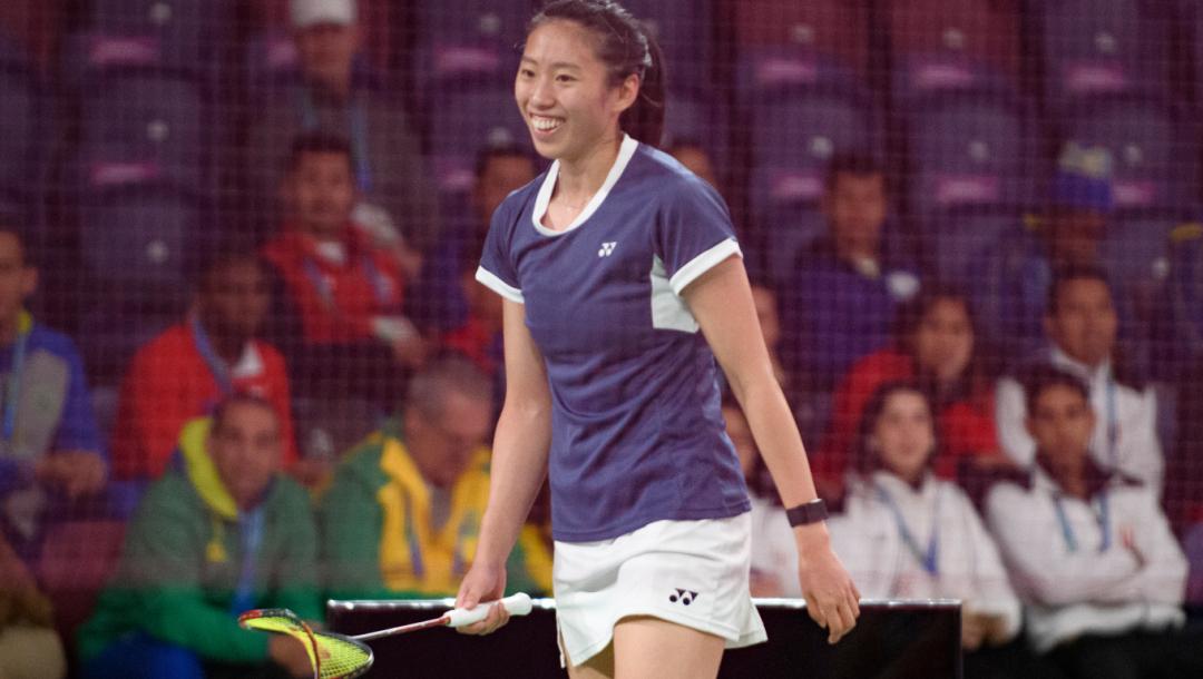 Une joueuse de badminton sourit en plein match