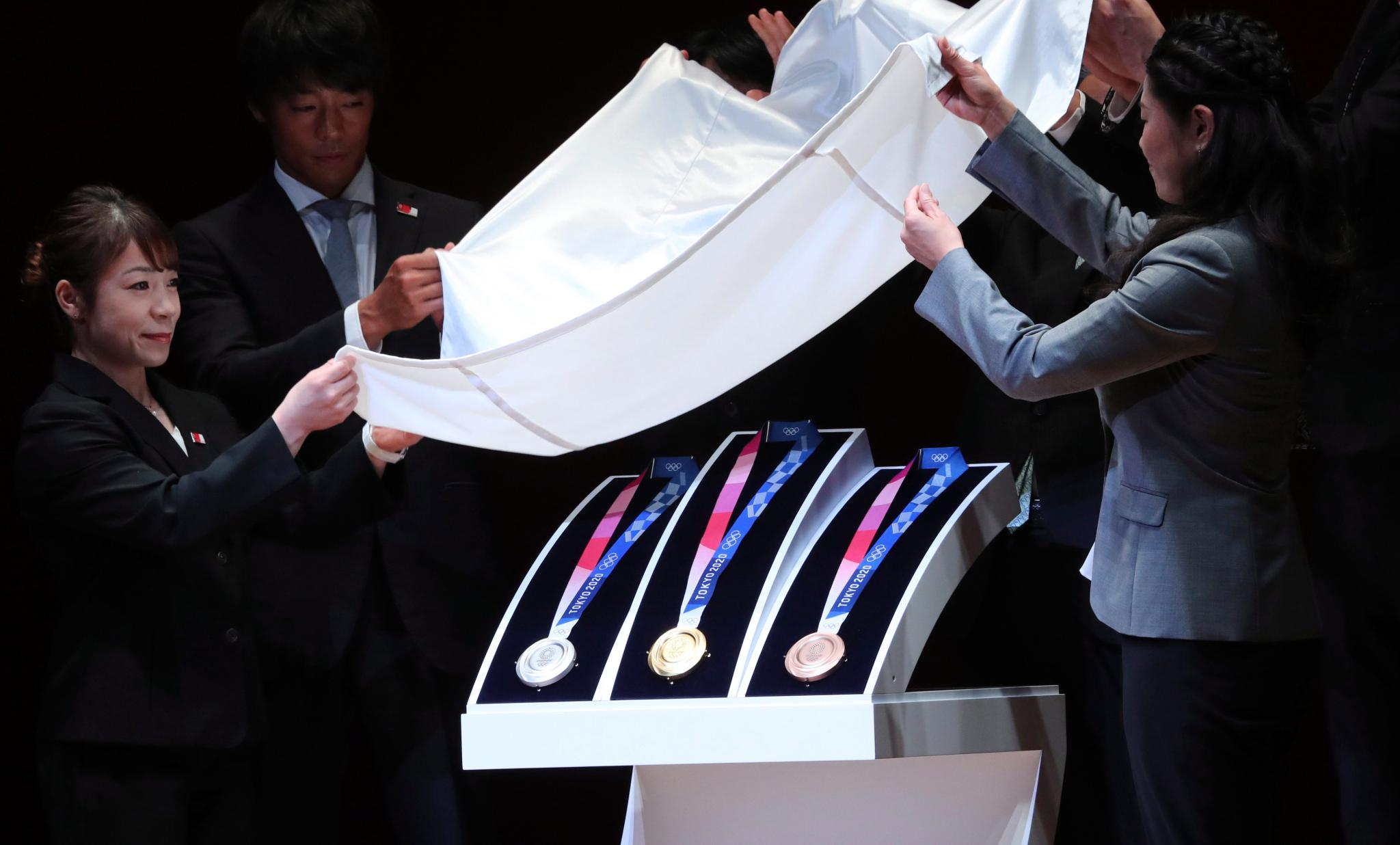 Deux personnes dévoilent des médailles