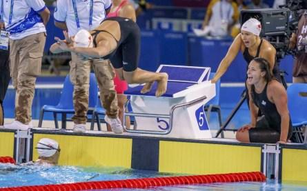 Des athlètes encouragent une nageuse qui plonge dans la piscine pendant une course