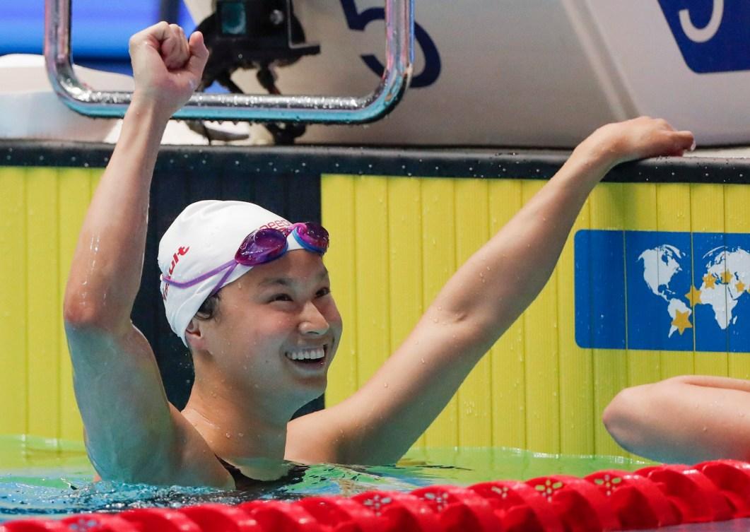 La nageuse Maggie Mac Neil lève le bras dans les airs après sa victoire aux Championnats du monde FINA 2019.