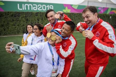 Eric Peters, Crispin Duenas et Brian Maxwell posent avec leurs médailles d'or et des bénévoles aux Jeux panaméricains de Lima, au Pérou, le 11 août 2019. Photo : Christopher Morris/COC