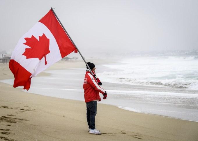 L'entraîneur de Mathea Olin avec le drapeau canadien lors de la finale de longboard féminin des Jeux panaméricains de Lima 2019, le 4 août 2019. Photo : Vincent Ethier/COC