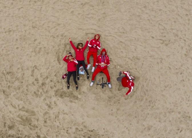 Les membres de l'équipe canadienne de surf allongés sur la plage aux Jeux panaméricains de Lima 2019, le 1er août 2019. Photo : Vincent Ethier/COC