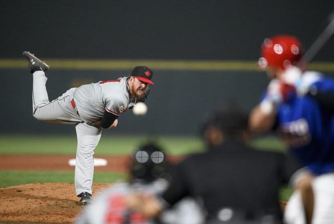 Un joueur de baseball lance une balle vers le batteur