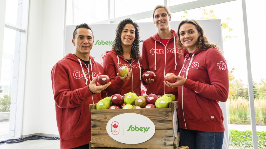 Quatre athlètes d'Équipe Canada sourient avec une pomme à la main.