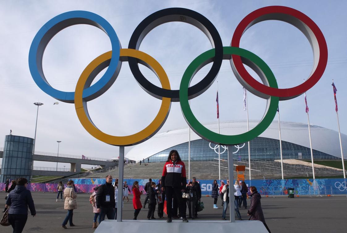 Shanti, une bénévole d'Équipe Canada, pose devant les anneaux olympiques dans le Parc olympique de Sotchi 2014.