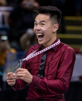 Nam Nguyen fait un grand sourire en montrant sa médaille d'argent.