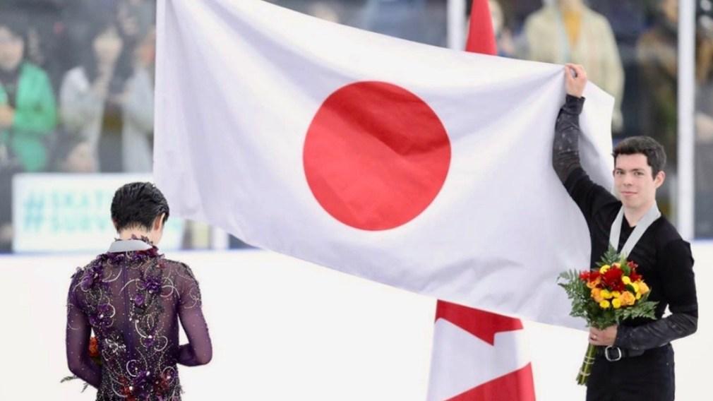 Keegan Messing tient le drapeau Japonais pour Yuzuru Hanyu lors de l'hymne national du Japon.