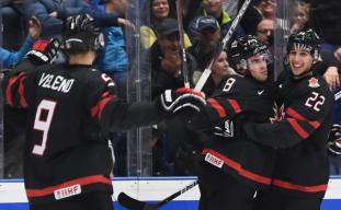 Trois joueurs canadiens célèbrent un but.