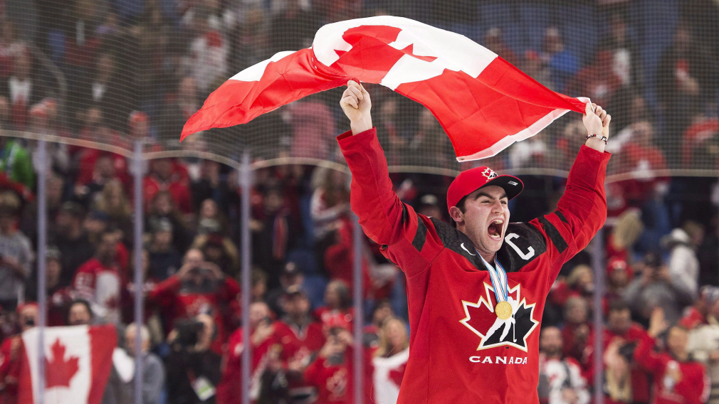 Dillon Dubé réagit et pote le drapeau canadien après une victoire