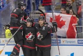 Trois joueurs d'Équipe Canada célèbrent après un but