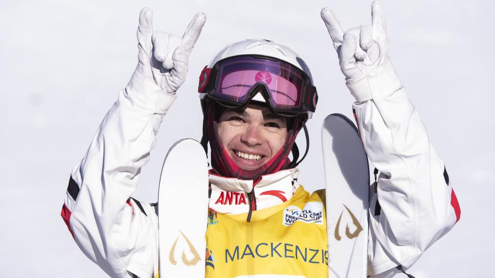 Un skieur fait des signes de rock avec ses mains