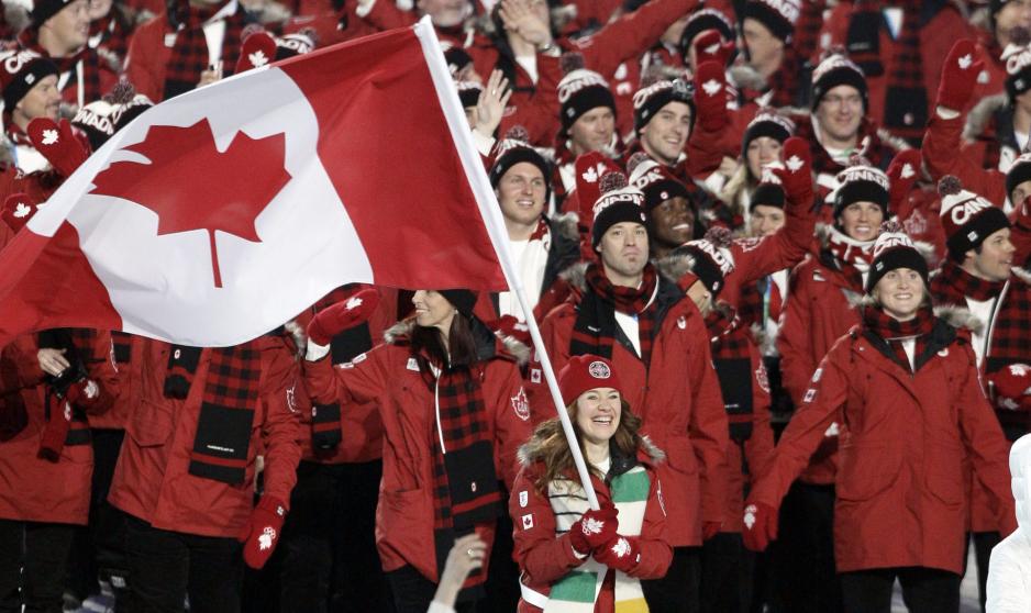 Clare Hugues en avant-plan mène l'équipe canadienne dans le stade.