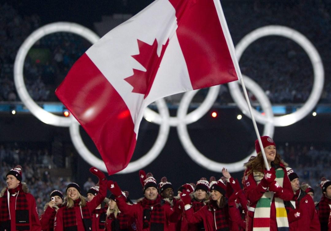 Clara Hughes porte le drapeau canadien, l'équipe canadienne derrière elle.