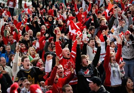 Des fans de hockey canadiens jubilants célèbrent la victoire de 3-2 du Canada contre les États-Unis en prolongation, en finale pour l'or aux Jeux olympiques de Vancouver 2010, au centre-ville de Vancouver, le 28 février 2010. (AP Photo/Kevin Frayer)