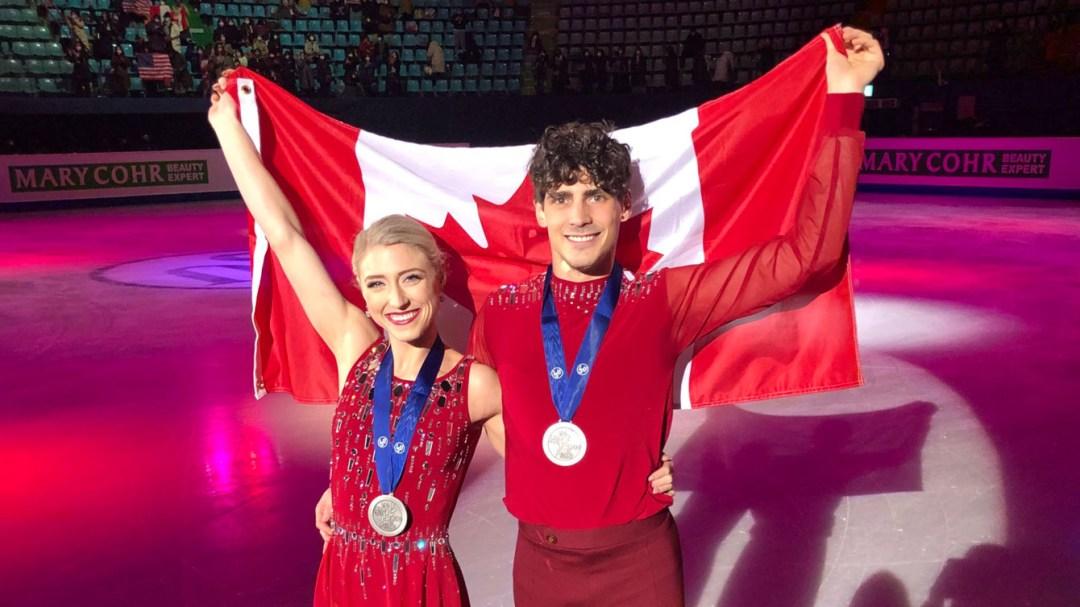 Deux patineurs posent avec le drapeau canadien et leurs médailles d'argent sur la patinoire