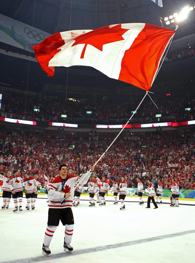 Sidney Crosby tient le drapeau canadien sur la patinoire