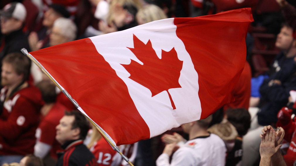 UN drapeau canadien flotte dans la foule lors d'un match de hockey de Vancouver 2010