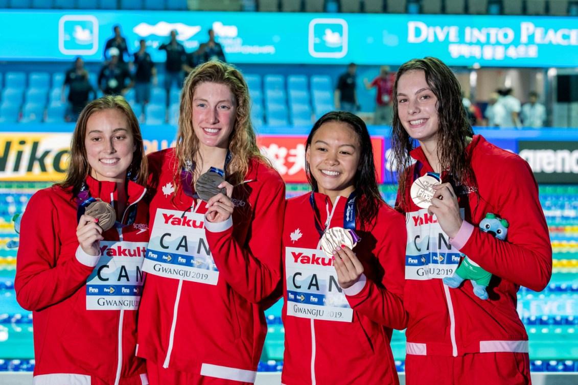 Quatre nageuses canadiennes posent avec leurs médailles.