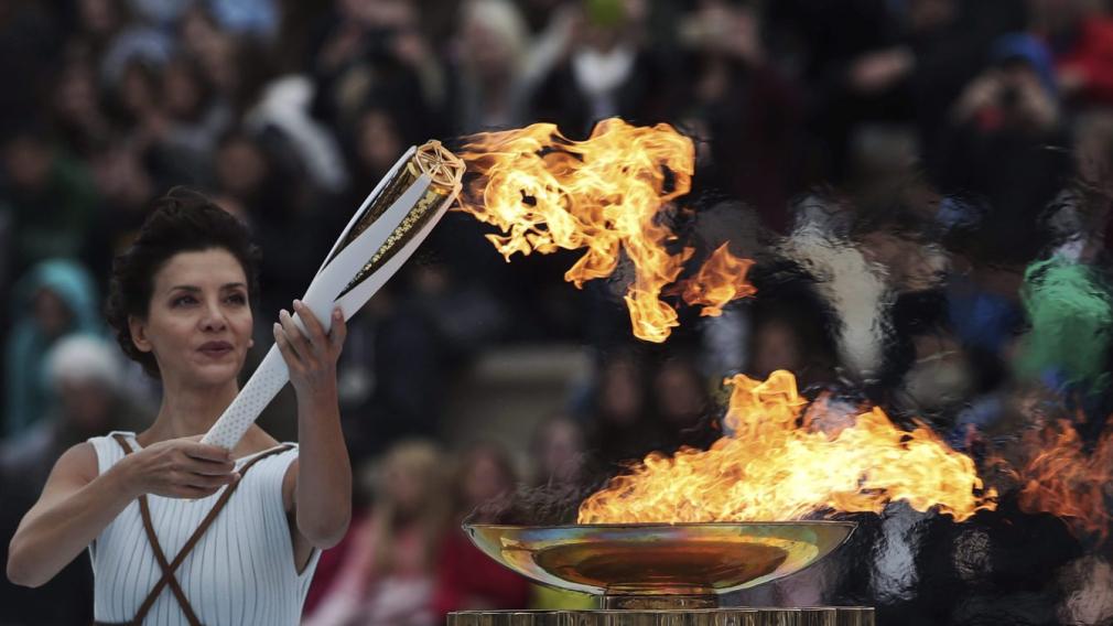 Une femme vêtue en citoyenne de la Grèce antique allume la flamme olympique