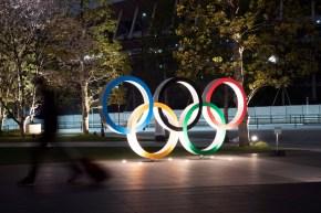 Les anneaux olympiques illuminés dans la nuit.