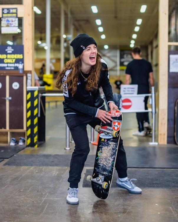 Annie Guglia rit en tenant son skateboard