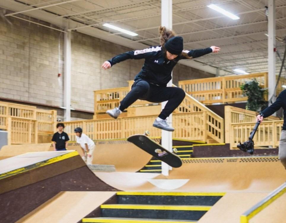Annie Guglia effectue un saut en skateboard au-dessus d'une rampe.