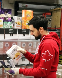 Joseph Polossifakis aide a déballer les produits de la cargaison d'Équipe Canada. (MOISSON MONTRÉAL/ALEXANDRA GRENIER)