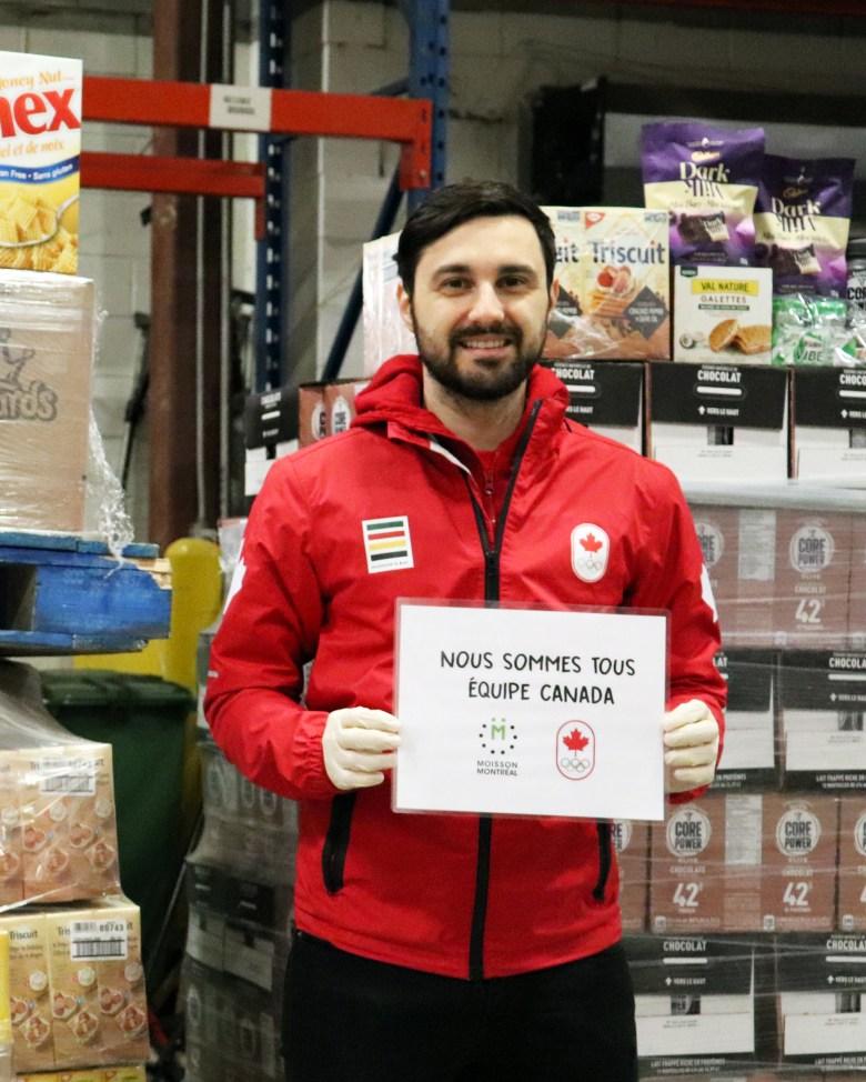 Joseph Polossifakis montre une affiche sur laquelle il est inscrit « Nous sommes tous Équipe Canada »