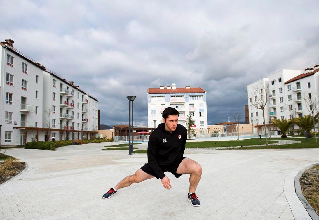 Vincent De Haître fait un étirement au milieu du village des athlètes