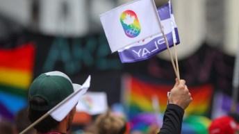 Un drapeau arc en ciel pendant une manifestation.