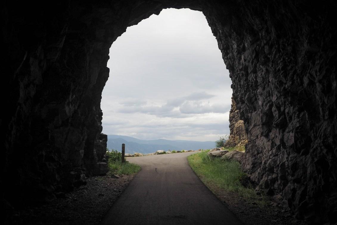 La fin d'une grotte, qui s'ouvre sur une piste cyclable et la vue d'une forêt.