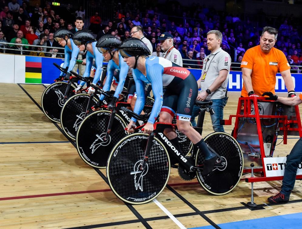 Quatre cyclistes sur la ligne de départ dans un vélodrome