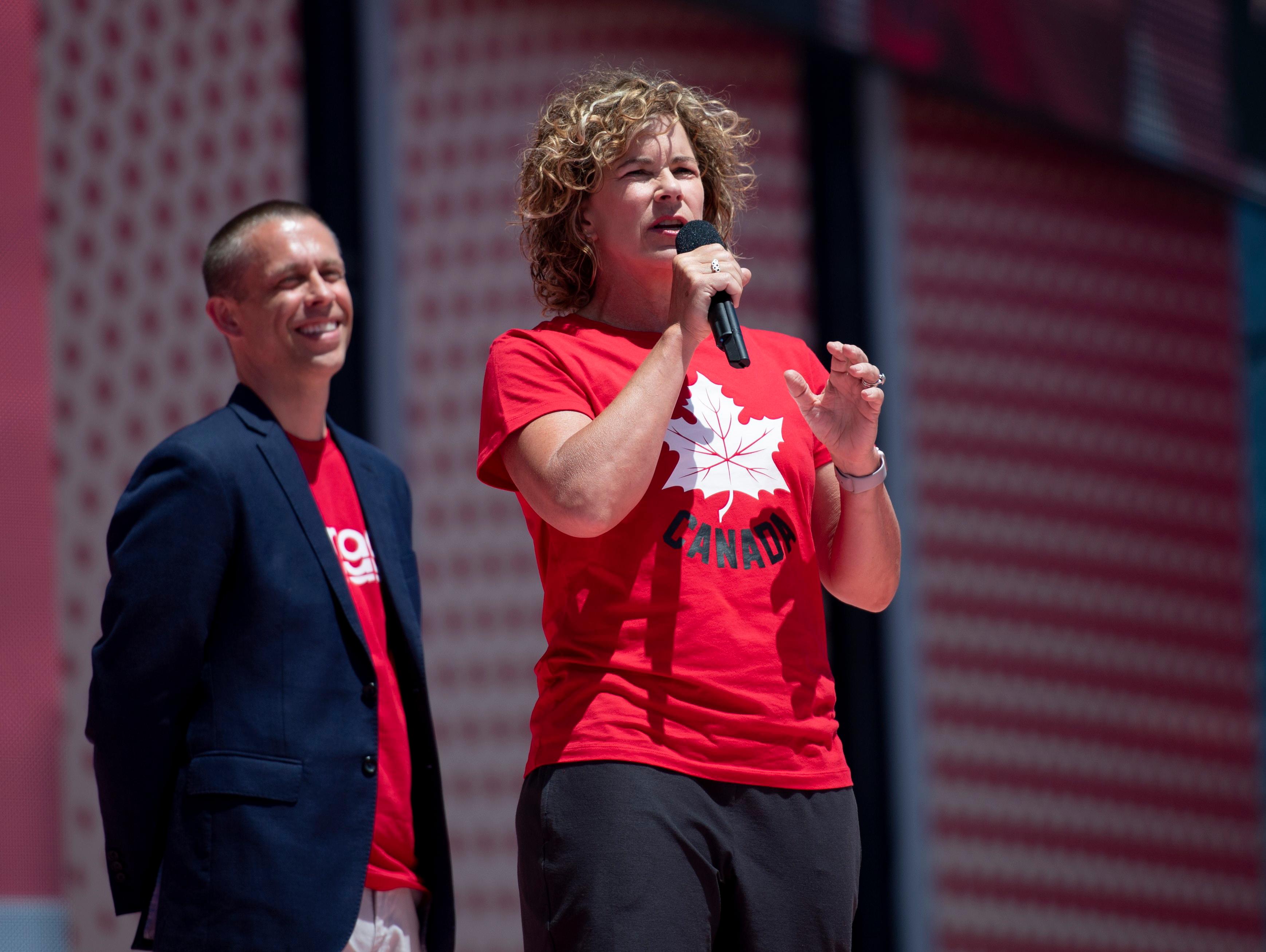 Marnie McBean s'adresse à une foule avec un micro en main.