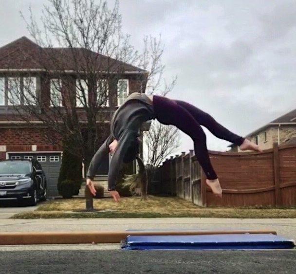 Ana Padurariu en suspension dans les airs, tête à l'envers, au-dessus de la poutre.