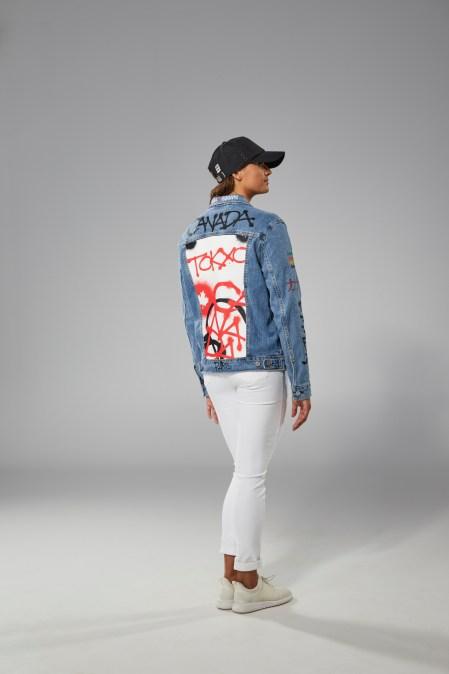 Kylie Masse porte un jeans blanc, un t-shirt noir et une veste en jeans