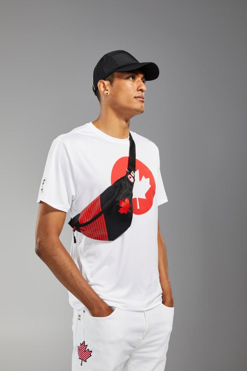 Pierce LePage porte un t-shirt blanc, un sac banane, une casquette noire et des jeans blancs