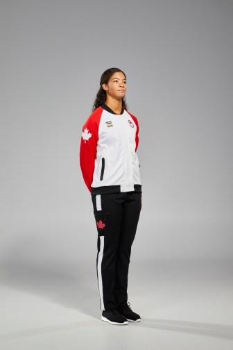 Sarah Douglas porte une veste rouge et blanche avec des pantalons noirs